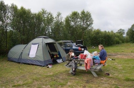 Mother with children sit at  table about tent near  car on  nature photo