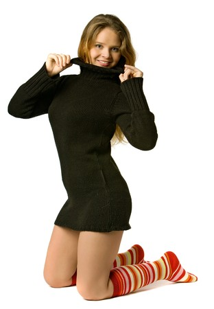 woolen: beautiful girl in a long sweater and colored golfs stands on knees, isolated on white