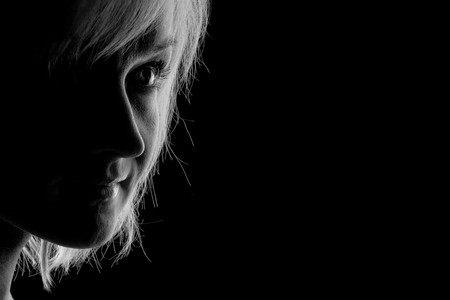 young woman fine-art high-contrast portrait in backlight photo
