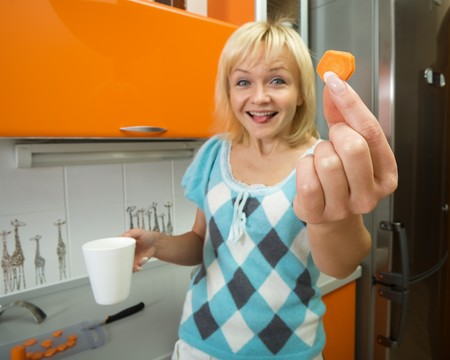 young smiling woman holds a bit of carrot in hands photo