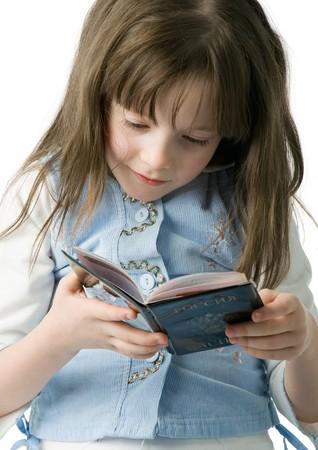� fond: belle petite fille regarde attentivement dans un passeport, isol� sur blanc Banque d'images