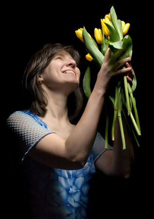 A beautiful woman in blue clothes catches yellow tulips on black background photo