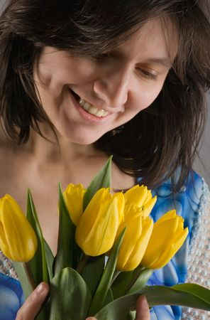 A beautiful woman with a smile looks at the bouquet of yellow tulips photo