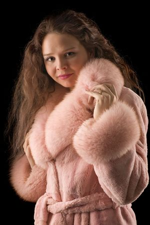 sexy fur: A beautiful romantic girl in a pink fur coat with long hair looks in camera on black background