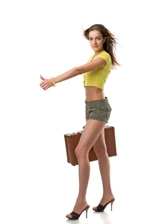 beautiful girl in clothes with a suitcase stops an auto, isolated on white Stock Photo - 4711858