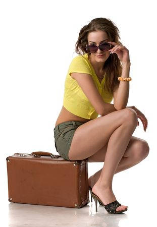 beautiful girl in sun glasses and clothes sits on a suitcase, isolated on white