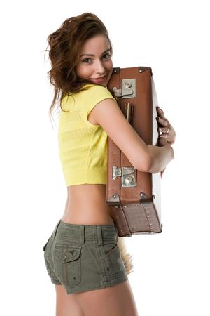 beautiful smiling girl in shorts and shirt hugs a suitcase