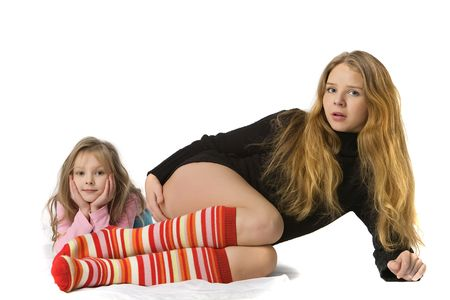 surprised mother with long hairs and daughter lie on the floor, isolated on white photo