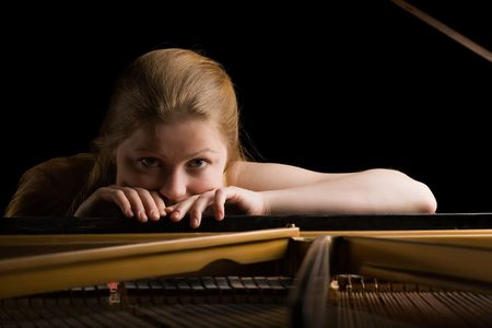 beautiful thoughtful girl laid hands on the lid of piano and looks in camera photo