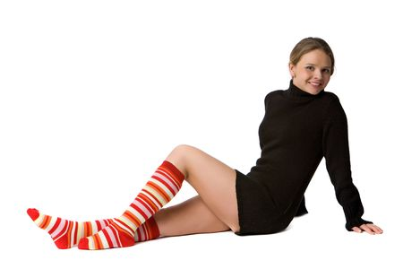 beautiful smiling girl in black sweater and long striped socks sits on the floor, isolated on white Stock Photo - 4751951