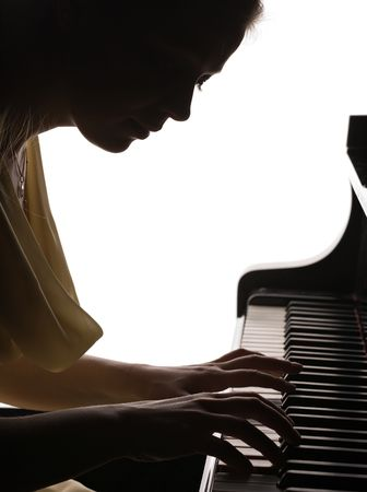 silhouette of beautiful girl playing the grand piano, isolated on white photo