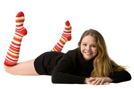 long socks: beautiful smiling girl in black sweater and long striped socks lies on the floor, isolated on white Stock Photo
