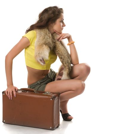 stole: beautiful girl in clothes and in stole sits near suitcase and looks aside, isolated on white Stock Photo