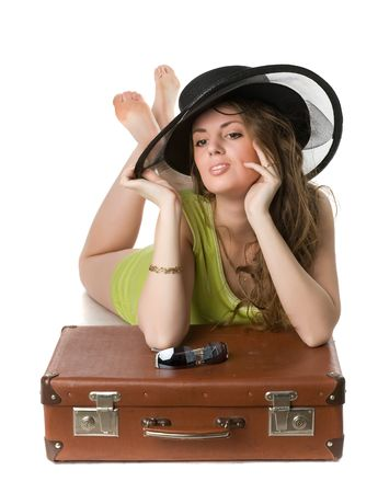 beautiful thoughtful girl in green dress and in a black hat lies on a suitcase photo