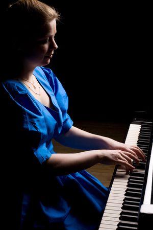 pianista: hermosa ni�a de vestido azul en la reproducci�n del piano de cola, aisladas en negro Foto de archivo