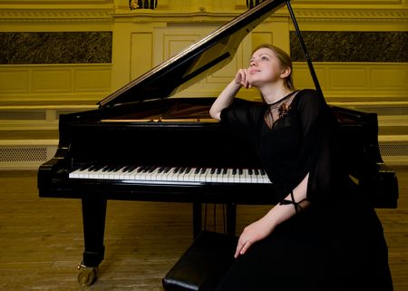 girl in black clothes sits near a piano and dreamily looks up