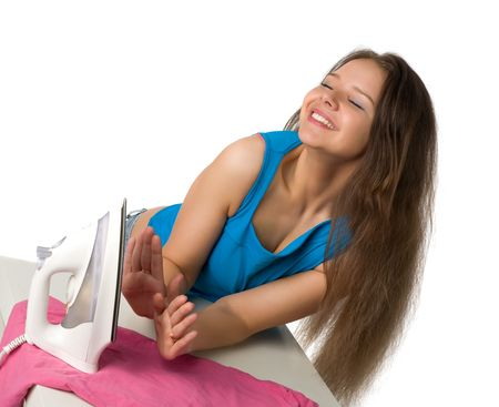 beautiful smiling girl with long hair warms ones hands about an iron, isolated on white photo
