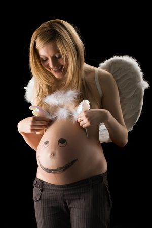 bared pregnant girl with wings dresses wings on a stomach with the drawn face on black background photo