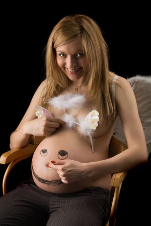 smiling bared pregnant woman with wings and the face drawn on a stomach presses a navel, isolated on black photo