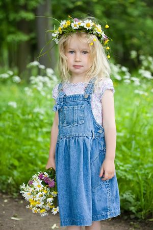 beautiful little girl in a wreath and with a bouquet looks in the camera photo