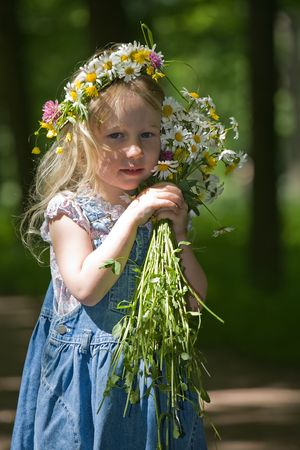 little  girl in a wreath and with a bouquet looks in camera photo