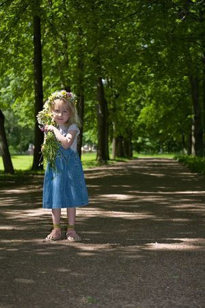 little girl in a wreath and with a bouquet stand  on path in park photo