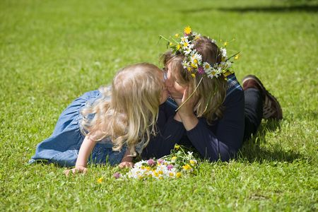 Mum and daughter lie on a green grass, the daughter kisses mum photo