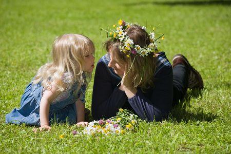 osiągnął: Mama i córka leżą na trawie, córka osiągnęła całować mama Zdjęcie Seryjne