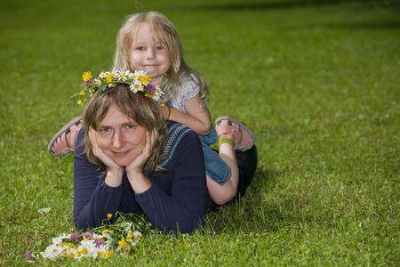 portrait of a mother lying on the lawn with her daughter sitting on her back, in the outdoors photo