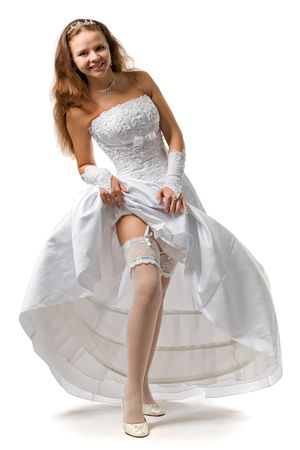 beautiful bride in a wedding dress shows a garter on a foot photo