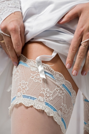 bride dresses stockings on feet, a close up photo