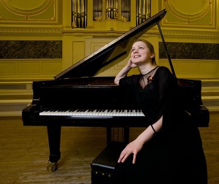 grand piano: girl in black clothes sits near a piano and dreamily looks up