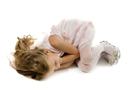 small princess with long hair sleeps on a floor, isolated on white photo