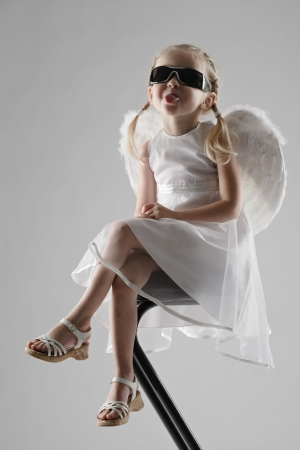 little girl dressed like an angel sitting on bar chair in dark glasses on gray background photo