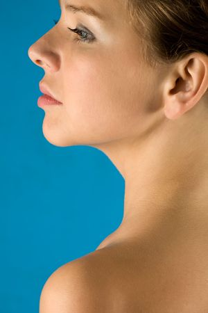 Profile of beautiful girl with a well-groomed skin on a dark blue background photo