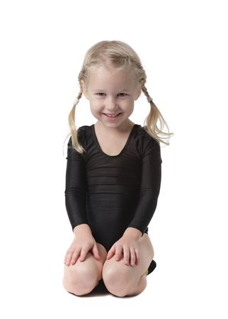 little gymnast girl sitting on knees isolated on white Stock Photo