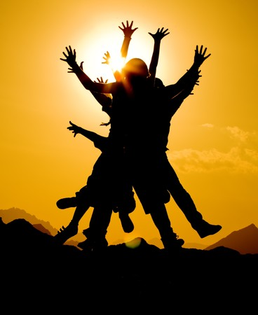 happiness people silhouette on the sunset: black silhouette of people group in happy jump on orange sunset sky and desert mountain background Stock Photo