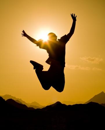 backlit: zwart silhouet van man in gelukkig sprong op oranje zonsondergang hemel en woestijn berg achtergrond