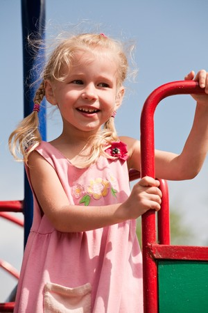 portrait of 5 years old blonde girl in summer pink dress on playground photo
