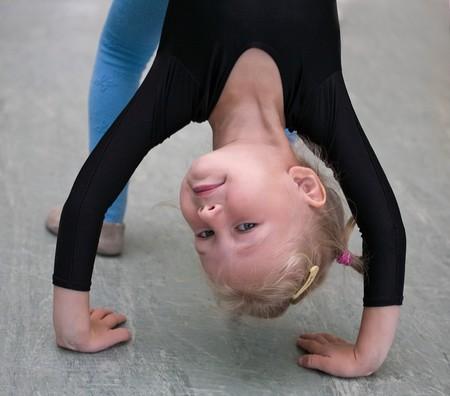 closeup of little gymnast girl doing exercises photo
