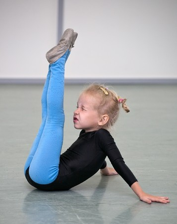 Гимнастика: little gymnast girl in gym