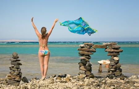piramide humana: mujer joven de pie en la playa de mar con chal de seda