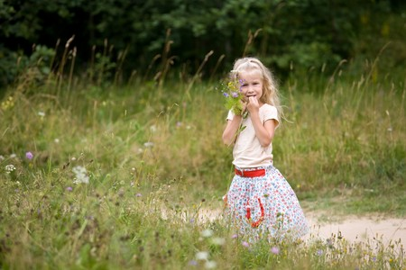 little beautiful blonde girl with bunch of wild flowers Stock Photo - 8213886