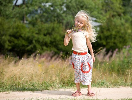 little blonde girl on a park walk with a bunch of wild flowers photo