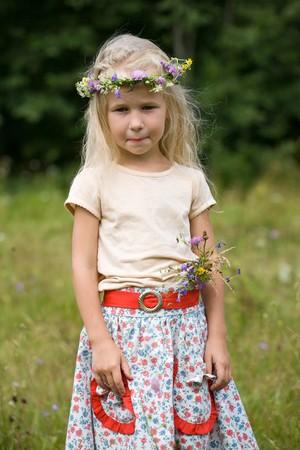 little blonde girl in wild flowers wreath on green meadow photo