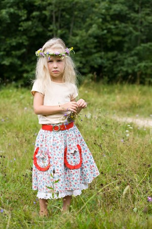 blonde girl with wild flowers on summer meadow photo