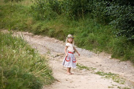 little girl in wild flowers wreath standing on road barefoot photo
