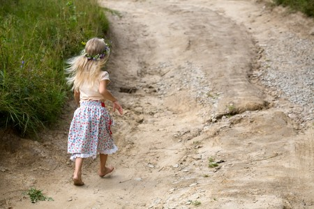 little girl in wild flowers wreath walking barefoot on summer road photo
