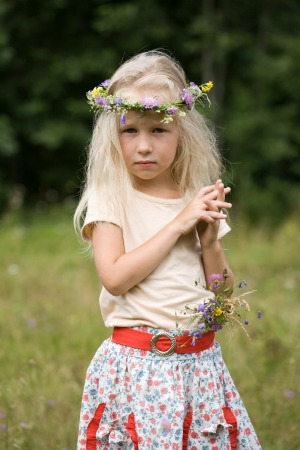 grass skirt: little long-haired blonde girl in wild flower wreath standing in the meadow