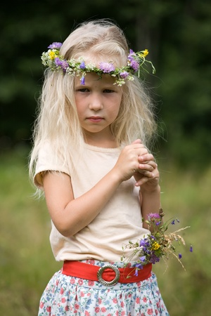 little long-haired blonde girl in wild flower wreath standing in the meadow photo